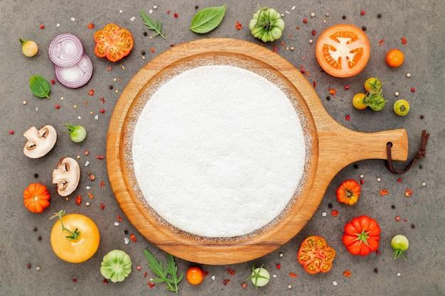 Gli ingredienti per la pizza fatta in casa impostati su sfondo di pietra scura. Foto Premium
