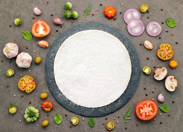 Gli ingredienti per la pizza fatta in casa impostati su sfondo di pietra scura.