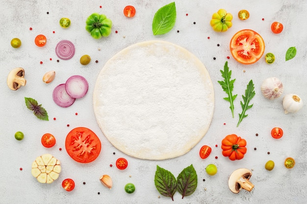 Gli ingredienti per la pizza fatta in casa impostati su uno sfondo di cemento bianco piatto e copiano lo spazio.