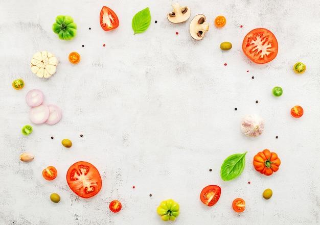 Gli ingredienti per la pizza fatta in casa allestiti su sfondo di cemento bianco.