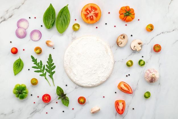 Gli ingredienti per la pizza fatta in casa allestiti su sfondo di marmo bianco con copia spazio e vista dall'alto.
