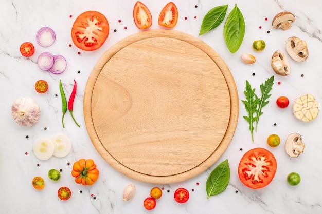 Gli ingredienti per la pizza fatta in casa allestiti su sfondo di marmo bianco.