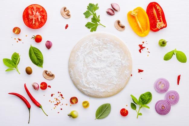 Gli ingredienti per la pizza fatta in casa su fondo di legno bianco.