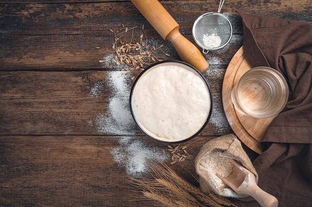 Ingredienti per fare il pane. coltivazione attiva di avviamento, farina di frumento e acqua su un fondo di legno marrone. vista dall'alto con copia spazio.