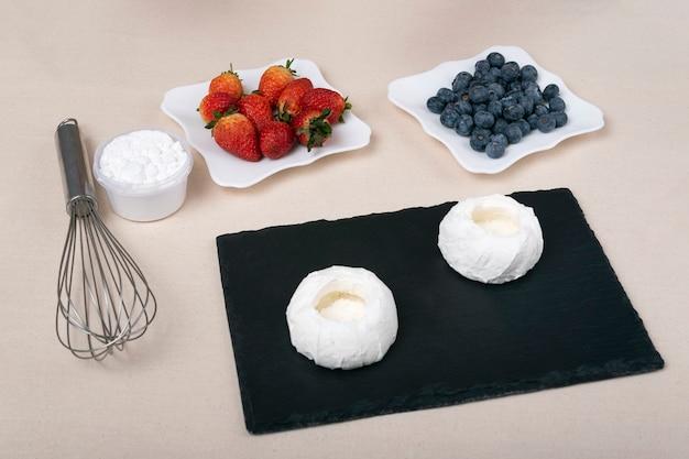 Ingredienti per fare torte alla frutta. frutti di bosco, biscotti, panna e frusta.