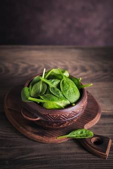 Ingredienti per preparare cibi vegani sani con barbabietole a fette. spinaci freschi in una ciotola di argilla su una superficie di legno rustica. mangiare pulito, concetto di cibo vegetariano