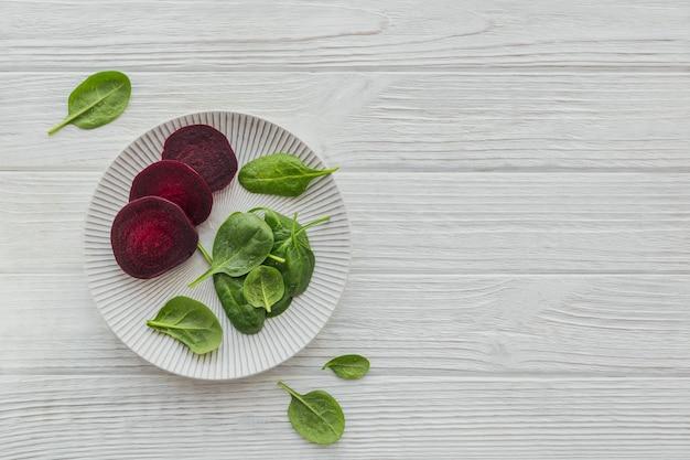 Ingredienti per preparare un sano cibo vegano con barbabietola rossa a fette e foglie di spinaci freschi su una superficie di legno bianca. mangiare pulito, concetto di cibo vegetariano