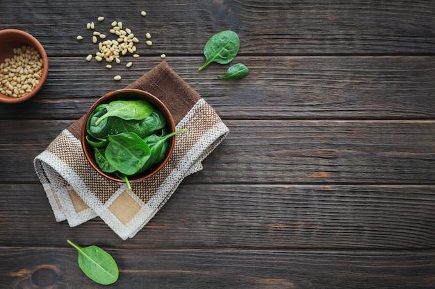 Ingredienti per preparare cibi vegani sani con barbabietole tagliate a fette, spinaci e pinoli. mangiare pulito, concetto di cibo vegetariano
