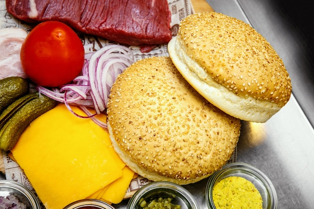 Ingredienti per preparare hamburger fatti in casa in cucina, serviti con carne