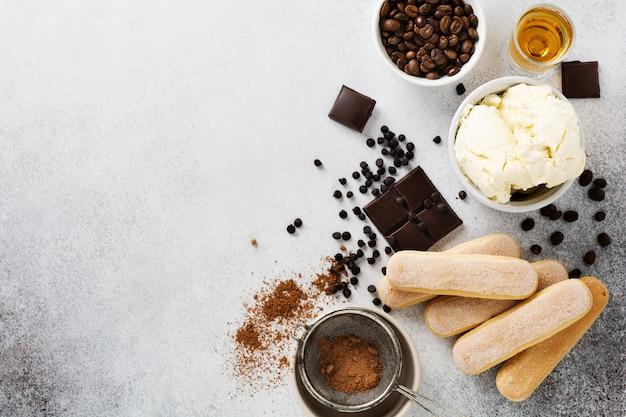 Ingredienti per preparare tiramisù dolce italiano, savoiardi, mascarpone, cacao in polvere e cioccolato su un cemento leggero