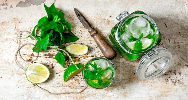 Ingredienti per preparare i mojito: lime, foglie di menta, rum, coltello per agrumi e un vecchio tavolo.