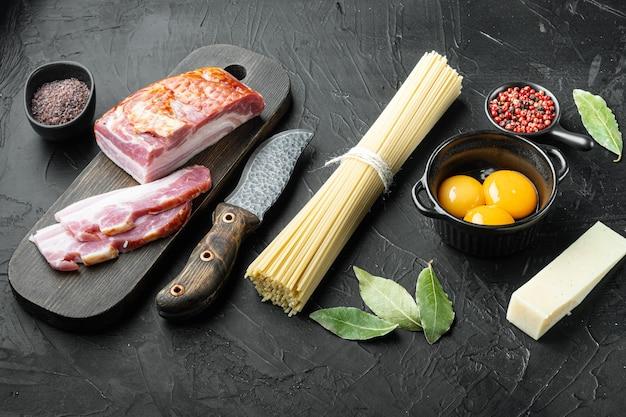 Ingredienti per fare la pasta alla carbonara prosciutto, set di pasta cruda, sul tavolo di pietra nera