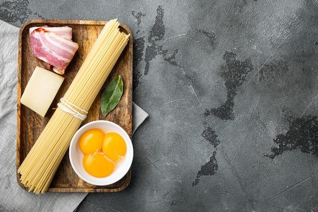 Ingredienti per fare la pasta alla carbonara prosciutto, set pasta cruda, su pietra grigia