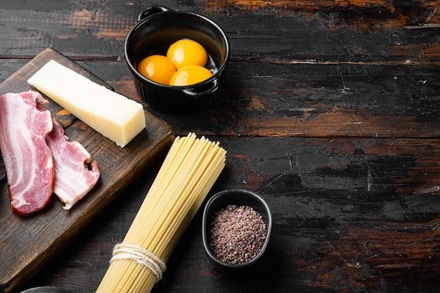 Ingredienti per fare la pasta alla carbonara prosciutto, set di pasta cruda, sulla vecchia tavola di legno scuro