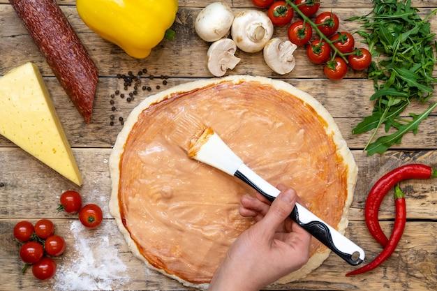 Ingredienti per fare la pizza, prima della cottura, su un tavolo di legno, impasto arrotolato spalmato a mano