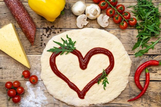 Ingredienti per fare la pizza, prima della cottura, su un tavolo di legno, vista dall'alto, ricetta passo passo