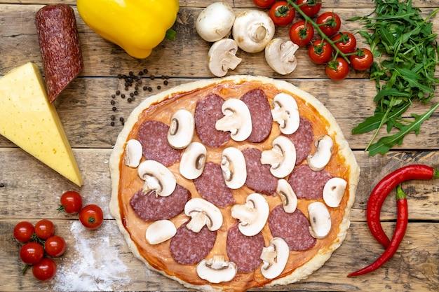 Ingredienti per fare la pizza e la pizza cruda prima della cottura, su un tavolo di legno, vista dall'alto.