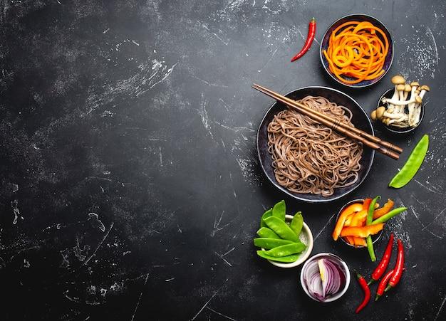 Ingredienti per fare i noodles saltati in padella soba. tagliare le verdure fresche, i funghi, le tagliatelle di soba bollite in una ciotola con le bacchette pronte per la cottura, sfondo di pietra nera, spazio per il testo, vista dall'alto