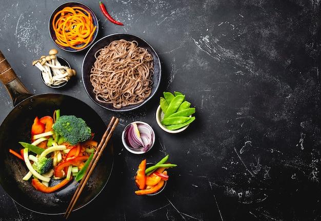 Ingredienti per fare i noodles saltati in padella soba. tagliare le verdure fresche in padella wok, le tagliatelle di soba bollite in una ciotola con le bacchette pronte per la cottura, sfondo di pietra nera, spazio per il testo, vista dall'alto