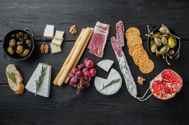 Ingredienti per la cucina mediterranea, carne cheede, set di erbe aromatiche, sul tavolo di legno nero, piatto lay