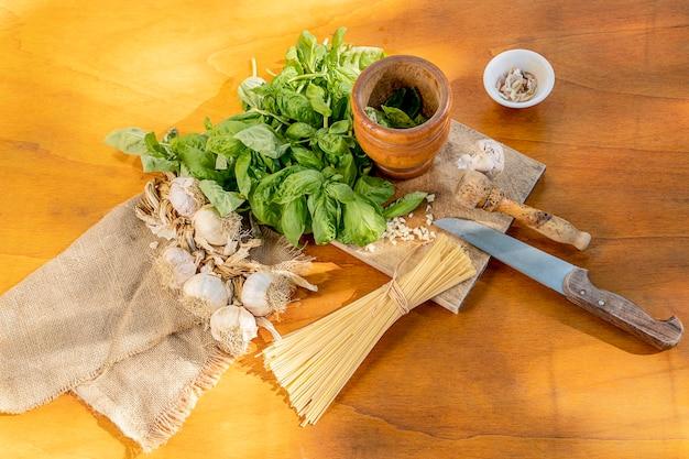 Ingredienti per una pasta mediterranea al pesto genovese su un tavolo di legno visto dall'alto