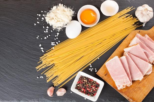 Ingredienti per la pasta alla carbonara su sfondo scuro di ardesia