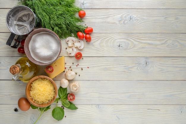 Ingredienti per pizza su una vista superiore del fondo di legno
