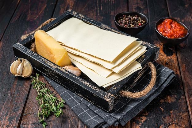 Ingredienti per la preparazione di lasagne, pomodori, salsa, pasta. fondo in legno scuro. vista dall'alto.