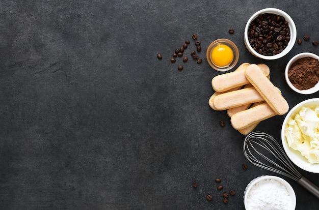 Ingredienti per preparare il tiramisù su sfondo nero. processo di cottura. dolce italiano classico.