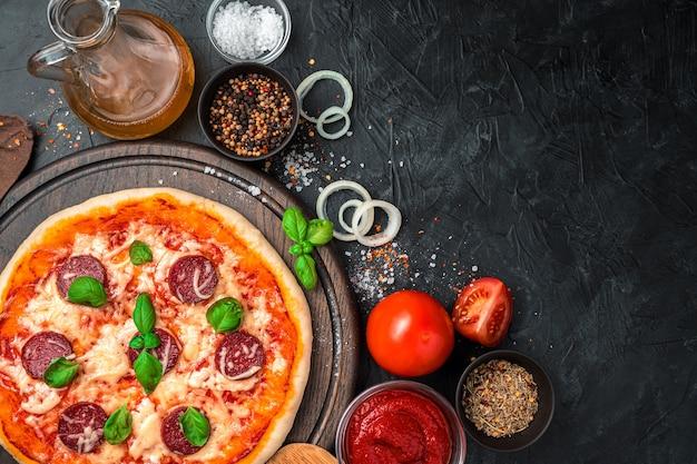 Ingredienti e pizza pronta su uno sfondo nero concreto