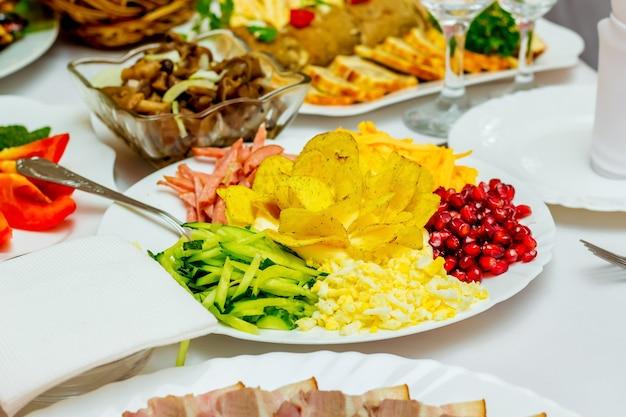 Ingredienti per la preparazione dell'insalata in un piatto al tavolo festivo del ristorante_