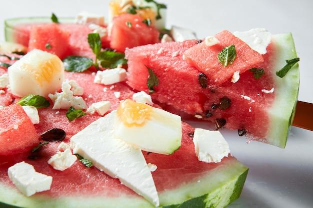 Ingredienti per l'insalata di fette di anguria e feta su uno sfondo bianco