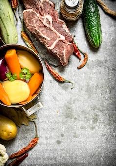 Ingredienti per zuppa con verdure, spezie e carne sul tavolo di pietra.