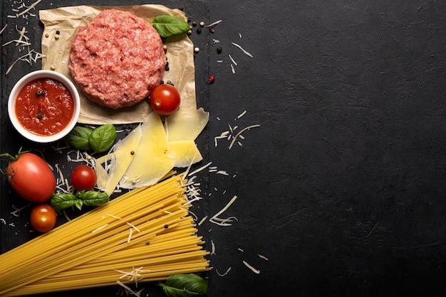 Ingredienti per spaghetti alla bolognese su sfondo nero, vista dall'alto