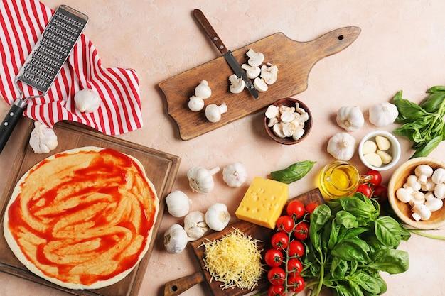 Ingredienti per una gustosa pizza sulla superficie del colore