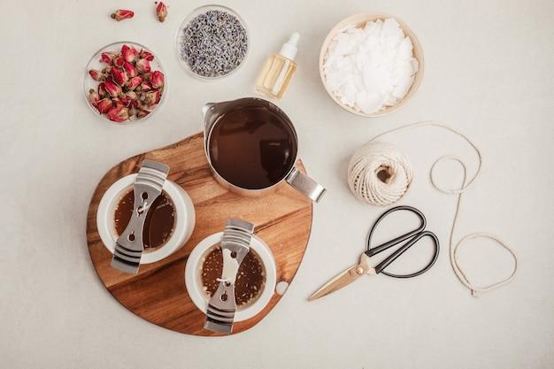 Ingredienti e strumenti per candele aromatiche fatte a mano. cera di soia biologica, oli essenziali, stoppini, pentole. hobby artigianale, piccola impresa, concetto di prodotti artigianali