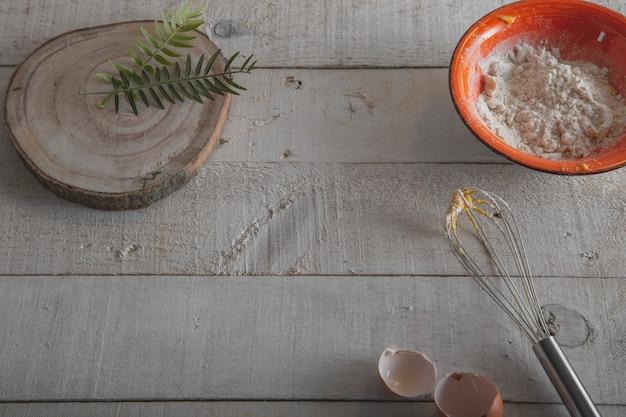 Ingredienti e strumenti per fare l'impasto, la farina, le uova e una frusta su un fondo di legno bianco.