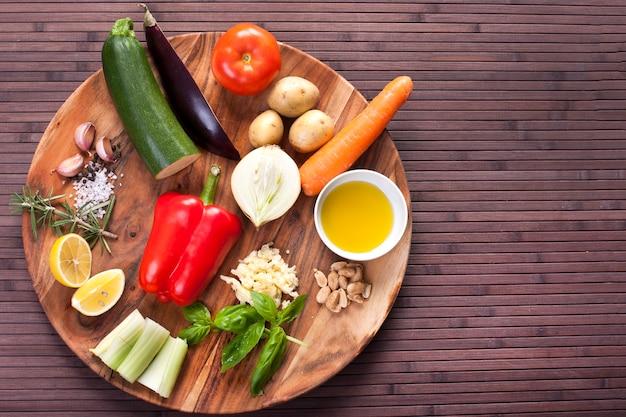Ingredienti verdure per zuppa con pesto e basilico su un piatto di legno. immagine di riserva.