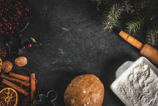 Ingredienti per, biscotti da forno invernali. pan di zenzero, torta di frutta. farina, mirtilli rossi, arance secche, cannella, spezie su un tavolo di pietra nera, vista dall'alto