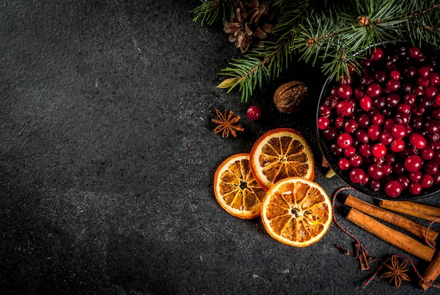 Ingredienti per, biscotti da forno invernali. pan di zenzero, torta di frutta, bevande di stagione. mirtilli rossi, arance secche, cannella, spezie su un tavolo di pietra nera, vista dall'alto