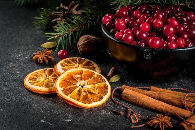 Ingredienti per, biscotti da forno invernali. pan di zenzero, torta di frutta, bevande di stagione. mirtilli rossi, arance secche, cannella, spezie su un tavolo di pietra nera,