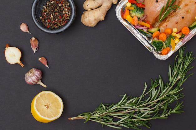 Ingredienti con copia spazio. petti di pollo al forno, aglio, cipolla, limone, peperoni in una ciotola e rosmarino su sfondo nero. vista dall'alto.