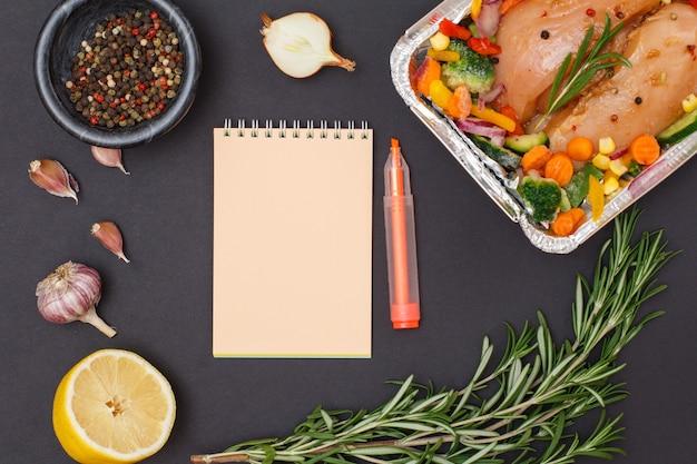 Ingredienti con copia spazio per ricetta di cucina. petti di pollo al forno, aglio, cipolla, limone, peperoni in una ciotola e rosmarino su sfondo nero. vista dall'alto.