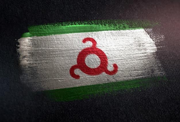 Bandiera di inguscezia fatta di vernice spazzola metallica sulla parete scura del grunge