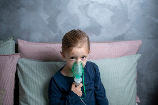 Inalazione, aerosol, una bambina di 6 anni fa l'inalazione in camera da letto contro un muro grigio