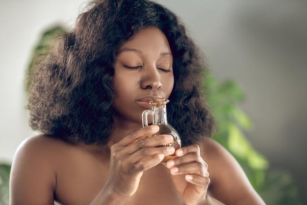 Inspira profumo. chiuda sulla giovane donna afroamericana abbastanza felice con gli occhi chiusi che tengono l'aroma vicino al viso