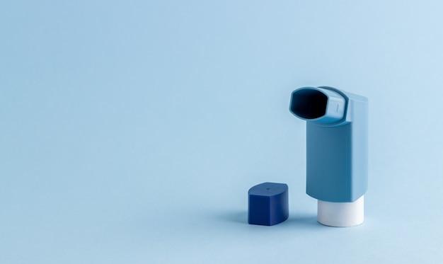 Inalatore su un tavolo blu. medicinale. salute. problemi respiratori.