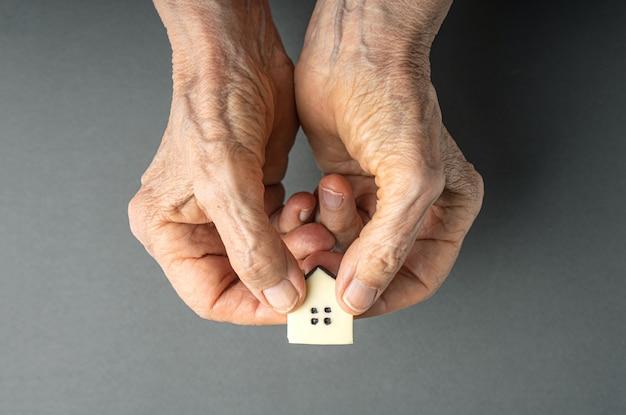 Concetto di ereditarietà. le mani della donna anziana danno una piccola casa del giocattolo.