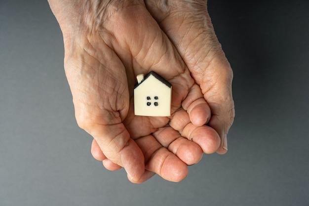 Concetto di ereditarietà. le mani della donna anziana tiene una piccola casa del giocattolo.
