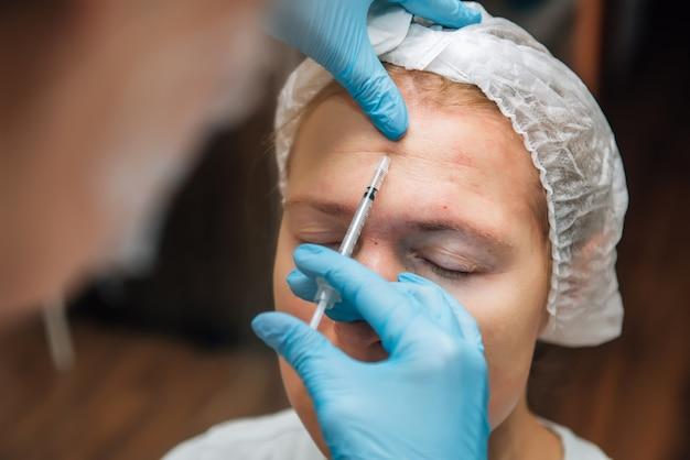 Iniezione di filler di acido ialuronico sotto la pelle sul viso della donna